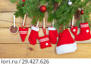 Christmas tree and a traditional red handmade toys hanging on a rope on a wooden background: Santa's hat, hearts, mittens and a gift sock. New Year still life. Стоковое фото, фотограф Виктория Катьянова / Фотобанк Лори