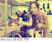 Купить «Woman looking after pair of shoes», фото № 29427770, снято 9 декабря 2018 г. (c) Яков Филимонов / Фотобанк Лори