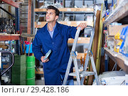 Купить «Man in unifom is using ladder to reach the top shelves in the building store.», фото № 29428186, снято 26 июля 2017 г. (c) Яков Филимонов / Фотобанк Лори
