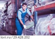 Купить «attentive male in uniform is choosing cement in the building store», фото № 29428202, снято 26 июля 2017 г. (c) Яков Филимонов / Фотобанк Лори