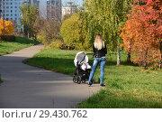 Купить «Женщина с коляской в парке на Мячковском бульваре. Район Марьино. Город Москва», эксклюзивное фото № 29430762, снято 16 октября 2018 г. (c) lana1501 / Фотобанк Лори
