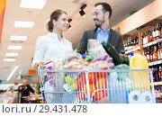 Купить «Couple is looking on shelves with variety products in the supermarket.», фото № 29431478, снято 4 апреля 2018 г. (c) Яков Филимонов / Фотобанк Лори