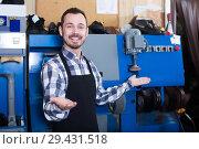 Купить «Laughing worker showing his workplace and tools», фото № 29431518, снято 2 февраля 2017 г. (c) Яков Филимонов / Фотобанк Лори
