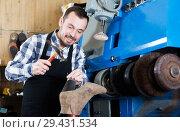 Купить «Male worker repairing shoe», фото № 29431534, снято 2 февраля 2017 г. (c) Яков Филимонов / Фотобанк Лори