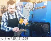 Купить «male worker fixing failed shoes in shoe repair workshop», фото № 29431538, снято 2 февраля 2017 г. (c) Яков Филимонов / Фотобанк Лори