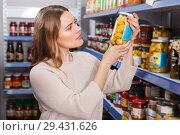 Купить «Serious female in the shop selection pickle goods indoor», фото № 29431626, снято 11 апреля 2018 г. (c) Яков Филимонов / Фотобанк Лори