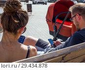 Молодые родители сидят на скамейке в парке с телефонами в руках (2018 год). Редакционное фото, фотограф Вячеслав Палес / Фотобанк Лори
