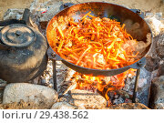 Купить «Uzbek pilaf in large in a cast-iron cauldron is cooked on a fire.», фото № 29438562, снято 15 июля 2017 г. (c) Акиньшин Владимир / Фотобанк Лори
