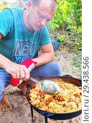 Купить «A young man cooks pilaf in a large cauldron on a fire.», фото № 29438566, снято 15 июля 2017 г. (c) Акиньшин Владимир / Фотобанк Лори