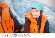 Купить «Mature woman in a life jacket goes on an inflatable boat on a beautiful river.», фото № 29438574, снято 15 июля 2017 г. (c) Акиньшин Владимир / Фотобанк Лори