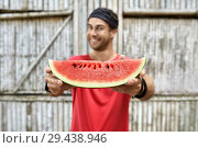 Smiling man with stubble holds slice of watermelon on wooden fence background. Стоковое фото, фотограф Andriy Bezuglov / Фотобанк Лори