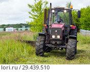 Купить «Скашивание травы на лугу с помощью трактора», эксклюзивное фото № 29439510, снято 5 июля 2018 г. (c) Вячеслав Палес / Фотобанк Лори