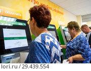 Купить «Оплата коммунальных услуг с использованием терминалов оплаты», фото № 29439554, снято 14 июля 2018 г. (c) Вячеслав Палес / Фотобанк Лори
