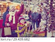 Купить «Attractive man with small daughter near Christmas decoration», фото № 29439682, снято 16 июня 2019 г. (c) Яков Филимонов / Фотобанк Лори