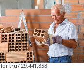 Купить «Man inspecting brick for installing wall», фото № 29441858, снято 19 июня 2018 г. (c) Яков Филимонов / Фотобанк Лори