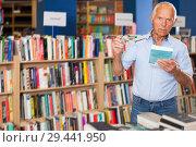 Купить «elderly male customer visiting bookshop in search of interesting fiction», фото № 29441950, снято 11 июня 2018 г. (c) Яков Филимонов / Фотобанк Лори