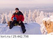 Купить «Male traveler sits resting on a cliff in the winter mountains and drinks tea from a thermos», фото № 29442798, снято 12 декабря 2017 г. (c) Евгений Харитонов / Фотобанк Лори
