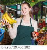 Купить «Portrait of seller woman who is standing with bananas on her workplace», фото № 29456282, снято 26 мая 2018 г. (c) Яков Филимонов / Фотобанк Лори