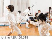 Купить «Active group practicing fencing techniques», фото № 29456318, снято 30 мая 2018 г. (c) Яков Филимонов / Фотобанк Лори
