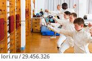 Купить «Group practicing fencing techniques in gym», фото № 29456326, снято 30 мая 2018 г. (c) Яков Филимонов / Фотобанк Лори