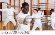 Купить «African American fencer practicing effective fencing techniques in training room», фото № 29456342, снято 30 мая 2018 г. (c) Яков Филимонов / Фотобанк Лори