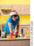 Купить «Young man cleaning kitchen after Christmas party», фото № 29459226, снято 27 июля 2018 г. (c) Elnur / Фотобанк Лори