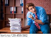 Купить «Young employee with excessive work sitting at the office», фото № 29459582, снято 29 августа 2018 г. (c) Elnur / Фотобанк Лори