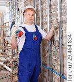 Купить «Construction worker using screw gun for aluminum profile mounting at indoors building site», фото № 29464834, снято 28 мая 2018 г. (c) Яков Филимонов / Фотобанк Лори