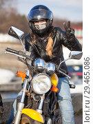 Купить «Девушка в шлеме на мотоцикле показывает знак победы рукой в кожаной перчатке», фото № 29465086, снято 30 апреля 2018 г. (c) Кекяляйнен Андрей / Фотобанк Лори