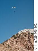 Купить «Paraglider is flying in the blue sky. Paragliding in the sky on a sunny day.», фото № 29466162, снято 4 сентября 2018 г. (c) Евгений Глазунов / Фотобанк Лори