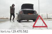 Купить «Winter Driving. Car Trouble. Car trouble on a snowy country road. A young man walks out of the car», видеоролик № 29470582, снято 27 января 2020 г. (c) Константин Шишкин / Фотобанк Лори