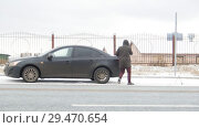 Купить «Winter Driving. Car Trouble. A troubled young man gets out of the car and walks to the the trunk», видеоролик № 29470654, снято 27 января 2020 г. (c) Константин Шишкин / Фотобанк Лори