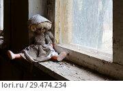 Кукла на подоконнике в заброшенном детском саде в уничтоженном селе Копачи, зона отчуждения Чернобыльской АЭС, Украина (2018 год). Стоковое фото, фотограф Ольга Коцюба / Фотобанк Лори