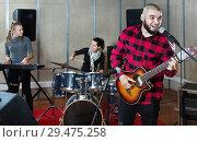 Купить «Bearded guy soloist playing guitar in studio», фото № 29475258, снято 26 октября 2018 г. (c) Яков Филимонов / Фотобанк Лори