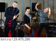 Купить «Three bandmates posing together with musical instruments in rehearsal room», фото № 29475286, снято 26 октября 2018 г. (c) Яков Филимонов / Фотобанк Лори