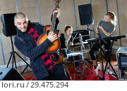 Купить «Guy guitar player and singer practicing with band members in recording studio», фото № 29475294, снято 26 октября 2018 г. (c) Яков Филимонов / Фотобанк Лори
