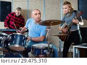 Купить «Expressive drummer with his bandmates practicing in rehearsal room», фото № 29475310, снято 26 октября 2018 г. (c) Яков Филимонов / Фотобанк Лори