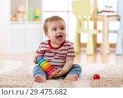 Купить «Baby toddler boy playing indoors with developmental toy sitting on soft carpet», фото № 29475682, снято 16 декабря 2018 г. (c) Оксана Кузьмина / Фотобанк Лори