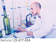 Купить «Mature man working on quality of products in winery lab», фото № 29477434, снято 12 декабря 2019 г. (c) Яков Филимонов / Фотобанк Лори