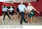 Купить «Active smiling people practicing lindy hop movements in dance class», фото № 29477578, снято 4 октября 2018 г. (c) Яков Филимонов / Фотобанк Лори