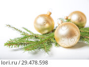Купить «Christmas decorations, three golden glass balls are lying on branch of Christmas tree, on  white background», фото № 29478598, снято 16 ноября 2018 г. (c) Юлия Бабкина / Фотобанк Лори