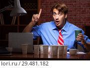 Купить «Young employee drinking coffee working at night shift», фото № 29481182, снято 28 августа 2018 г. (c) Elnur / Фотобанк Лори
