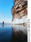 Купить «Lake Baikal. View of the cliffs of Olkhon island from the mirror ice at sunset. A photographer with a camera travels near the beautiful icy rocks», фото № 29484974, снято 8 марта 2015 г. (c) Виктория Катьянова / Фотобанк Лори