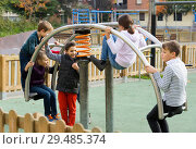 glad girl with long hair in school age sitting on swing on children's playground outdoors. Стоковое фото, фотограф Яков Филимонов / Фотобанк Лори
