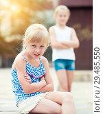 Купить «Small sisters upset after quarrel outside», фото № 29485550, снято 20 июля 2017 г. (c) Яков Филимонов / Фотобанк Лори