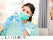 Купить «Girl nurse in mask holding syringe for injection in clinic», фото № 29485614, снято 1 мая 2018 г. (c) Яков Филимонов / Фотобанк Лори