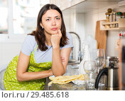 Купить «Tired girl housewife in apron holding gloves at kitchen», фото № 29485618, снято 18 апреля 2018 г. (c) Яков Филимонов / Фотобанк Лори