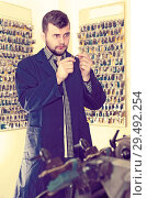 Купить «Worker displaying his tools for making keys», фото № 29492254, снято 5 апреля 2017 г. (c) Яков Филимонов / Фотобанк Лори