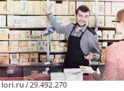 Купить «Seller assisting woman in choosing door hinges», фото № 29492270, снято 5 апреля 2017 г. (c) Яков Филимонов / Фотобанк Лори
