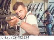 Купить «Portrait of adult man which is choosing air-powered gun», фото № 29492294, снято 4 июля 2017 г. (c) Яков Филимонов / Фотобанк Лори